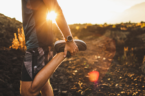 Male runner stretching leg and feet and preparing for running outdoors. Smart watch or fitness tracker on hand. Beautiful sun light on background. Active and healthy lifestyle concept. 1160478813