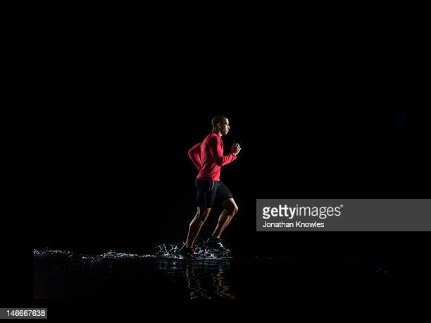 Male runner with red top on, running through water