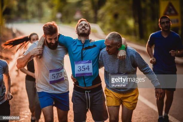 male runners carrying injured athlete during marathon in nature. - endurance stock photos and pictures