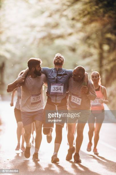 male runners carrying injured athlete during marathon race in nature. - a helping hand stock pictures, royalty-free photos & images