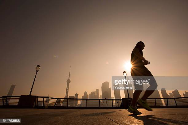 A male running at Shanghai bund in the morning,background is the Lujiazui,landmark of Shanghai