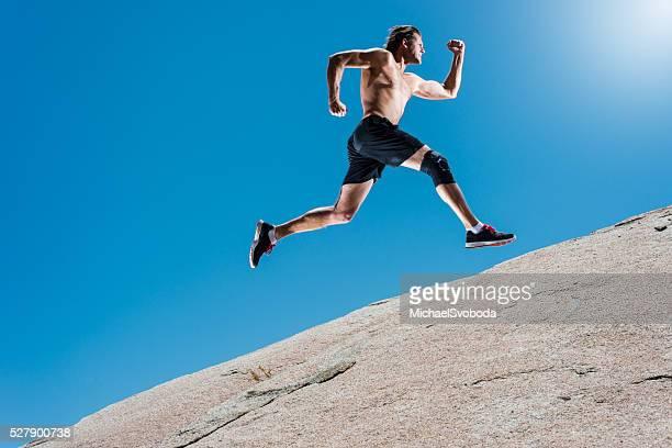 Männliche Laufen einen Granit-Boulder In den Bergen