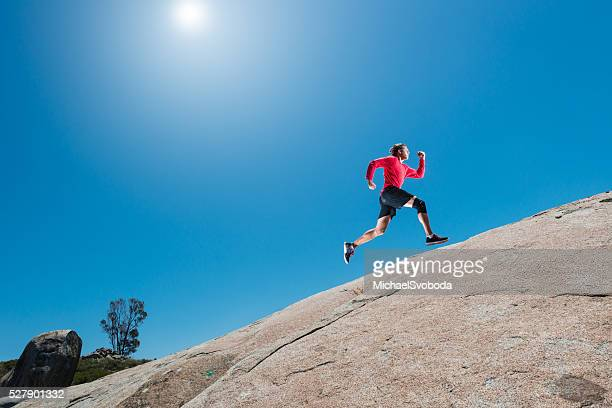 male running up a granite boulder in the mountains - uphill stock pictures, royalty-free photos & images