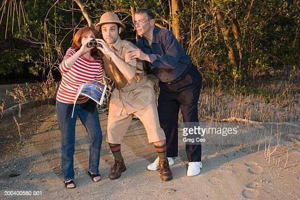 Male safari guide with couple, woman using binoculars