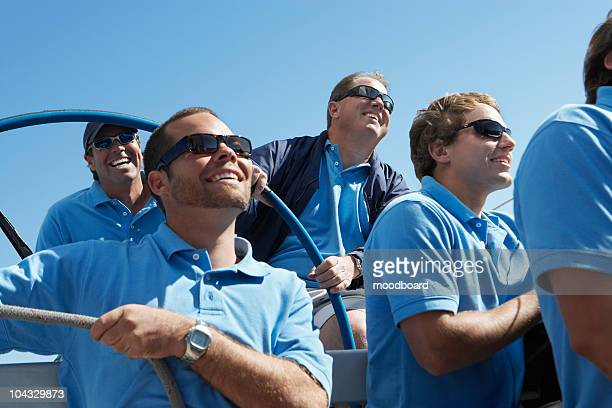 Male sailing team sitting on boat