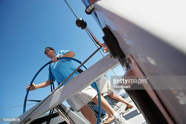Male sailor at steering wheel of boat
