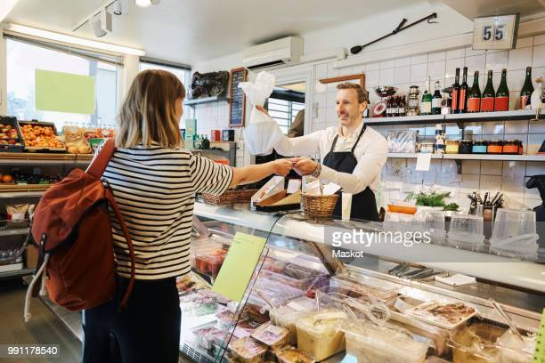 male sales clerk holding plastic bag while accepting credit card from customer at checkout counter - convenient store stock photos and pictures