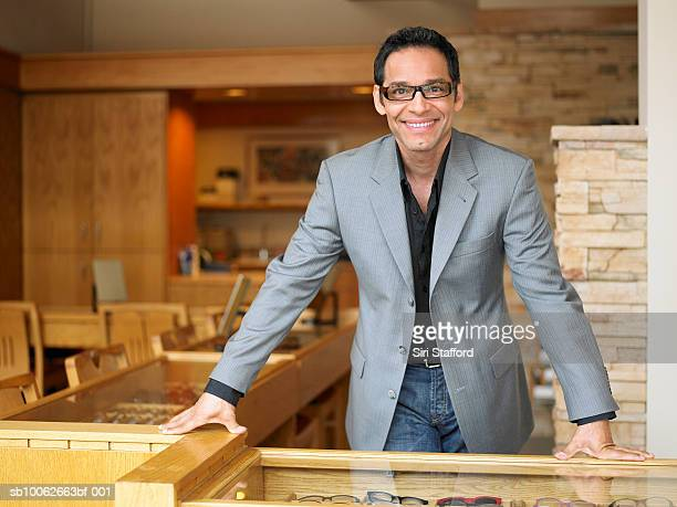 Male sales clerk standing in eyeglass store, portrait