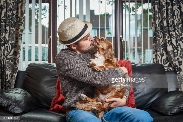 Male sat on a sofa cuddling his pet dog giving it a kiss