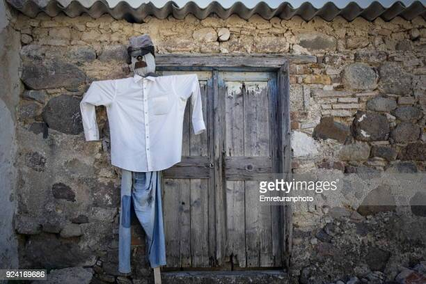 male scarecrow in front of a wooden door in barbaros village,izmir. - emreturanphoto stock pictures, royalty-free photos & images