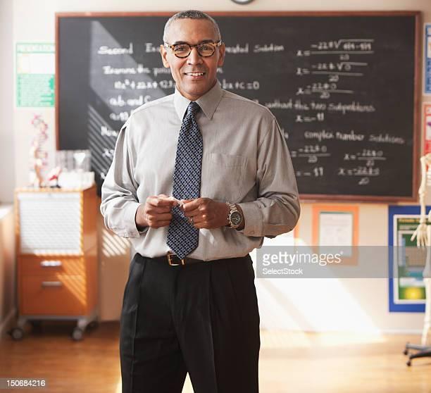 Male school teacher in front of blackboard