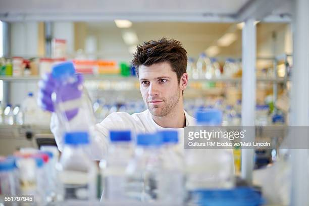 Male science student examining bottle in lab