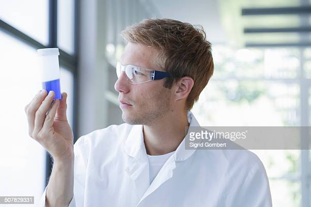 Male scientist analyzing sample in plastic bottle in lab