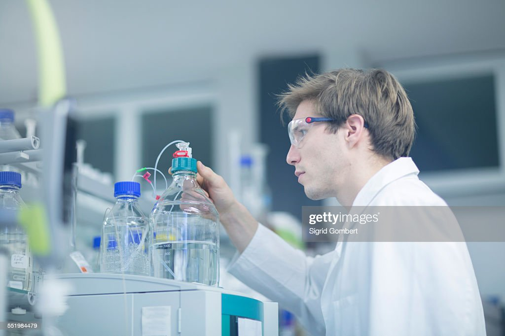 Male scientist checking experimental equipment in lab : Stock-Foto