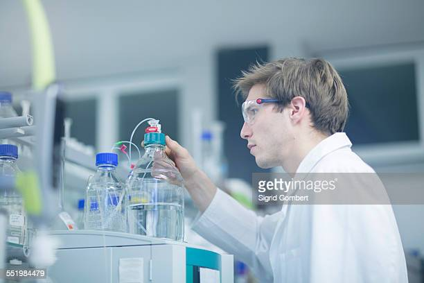male scientist checking experimental equipment in lab - sigrid gombert stock pictures, royalty-free photos & images