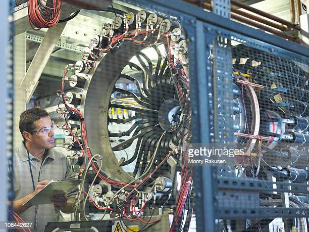 Male scientist inspects particle accelerator