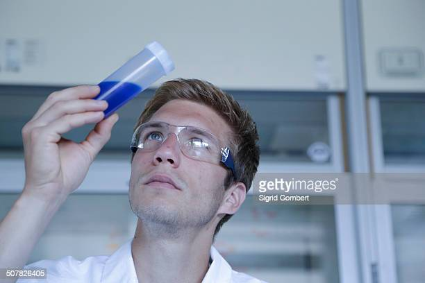 male scientist looking up at sample in plastic bottle in lab - sigrid gombert stock pictures, royalty-free photos & images