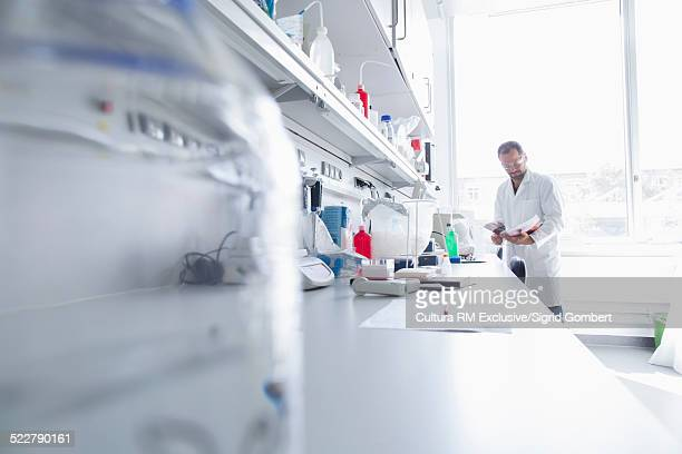 Male scientist reading science journal in biology laboratory