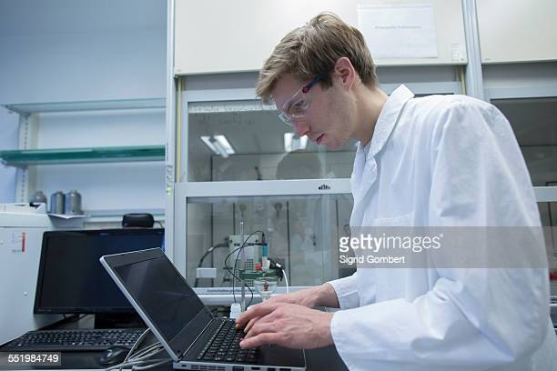 male scientist typing on laptop in lab - sigrid gombert stock-fotos und bilder