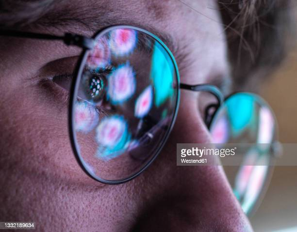 male scientist wearing eyeglasses with reflection of virus - epidemiology stock pictures, royalty-free photos & images