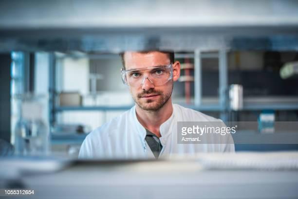 male scientist wearing protective eyewear in lab - bioquímico imagens e fotografias de stock