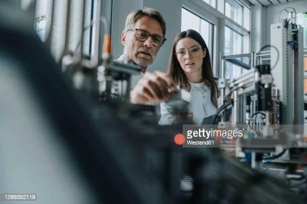 male scientist with young woman examining machinery in laboratory - ingenieurwesen stock-fotos und bilder