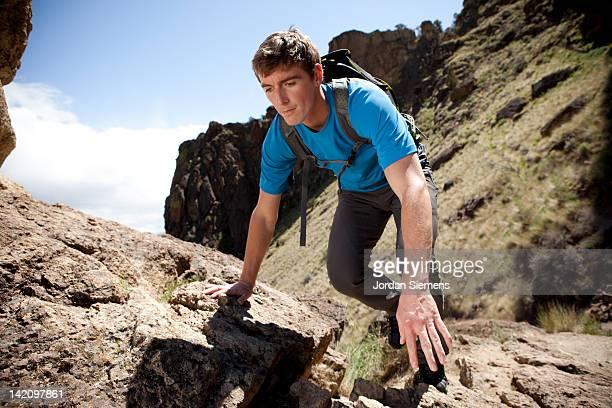 Male scrambling and hiking rocky trail.