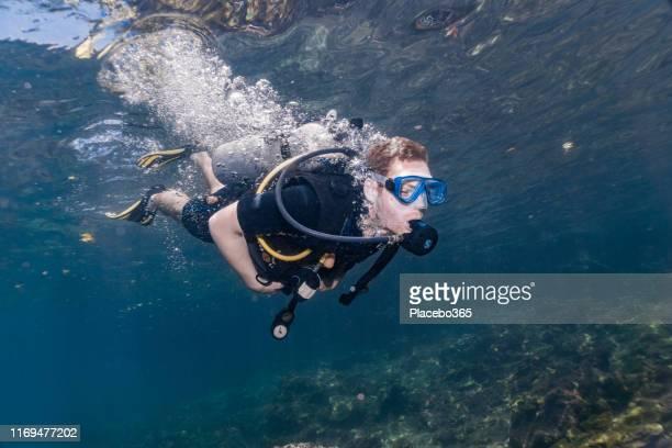 mannelijke scuba duiker duiken onderwater dragen aqualung - aqualung diving equipment stockfoto's en -beelden