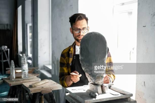 粘土バス保持ツールを仕上げる男性彫刻家 - 彫刻家 ストックフォトと画像