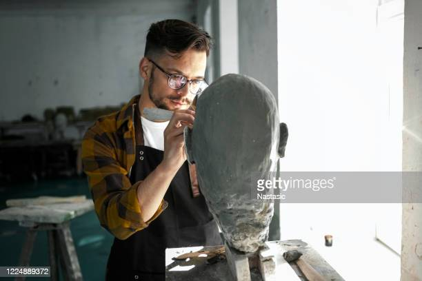 male sculptor working on a clay bust - sculpture stock pictures, royalty-free photos & images