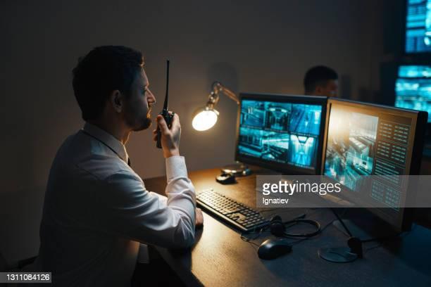een mannelijke bewaker 's nachts met een walkietalkie op de beveiligingsconsole houdt de beveiliging van het object nauwlettend in de gaten. - defending stockfoto's en -beelden