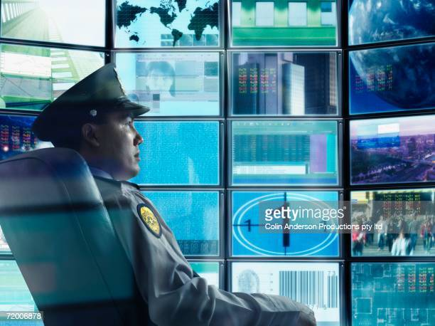Male security guard sitting in front of monitor screens