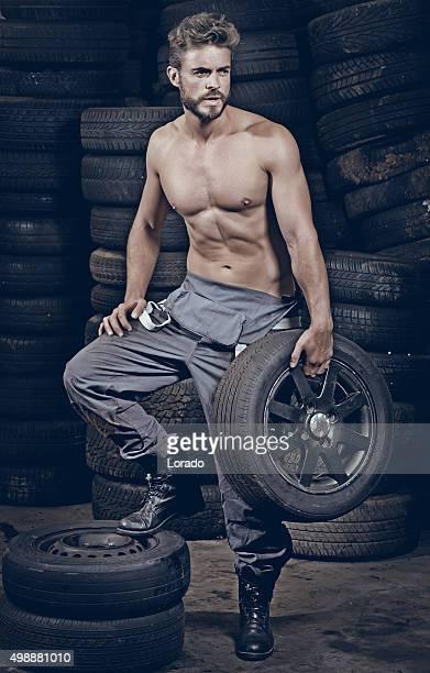 male halb angezogen Mechaniker sitzt auf der Vorderseite von Reifen