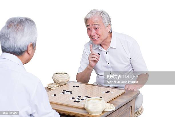 Male senior friends playing go