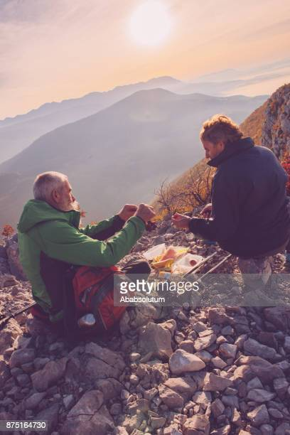 Male Senior Hikers Having Breakfast at Sunset in Southern Julian Alps, Europe
