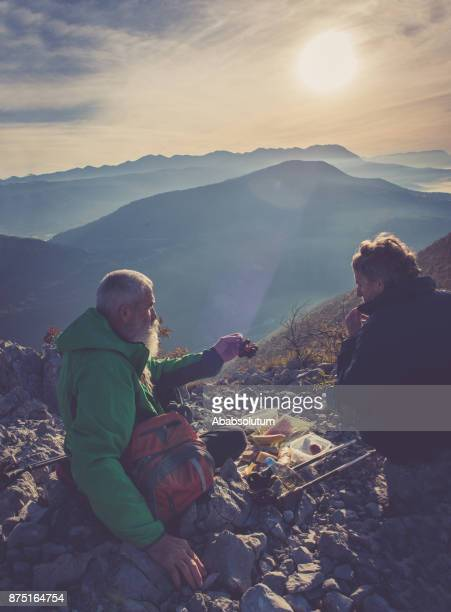 male senior hikers having breakfast at sunset in southern julian alps, europe - 60 69 years stock photos and pictures