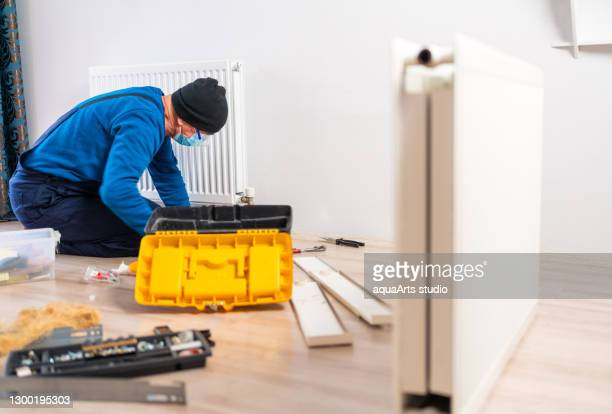 male senior plumber with protective face mask is repairing heating radiator in living room . heating restoration. home radiator montage.rusted radiator. - repairing stock pictures, royalty-free photos & images