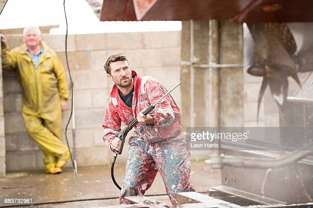 Male ship painter cleaning ship hull with pressure washer in ship painters yard
