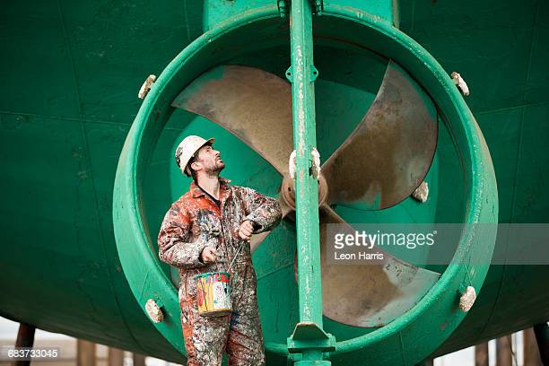 Male ship painter inspecting green ship hull in ship painters yard
