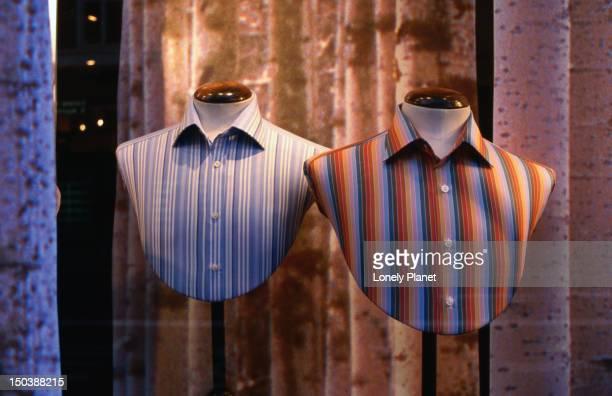 Male shirts on display in shop window.
