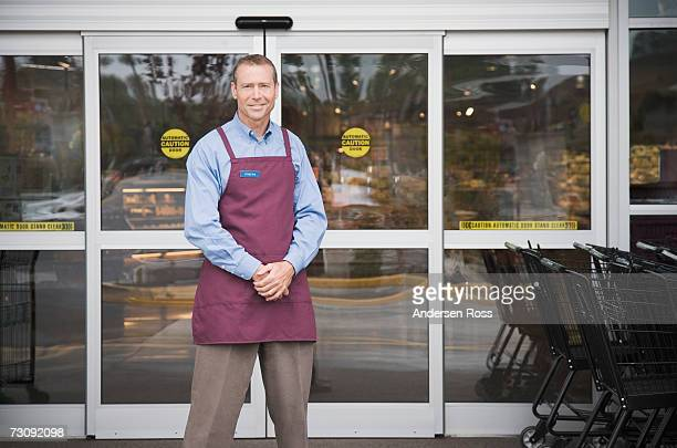 Male shop assistant standing in front of shop doors, portrait