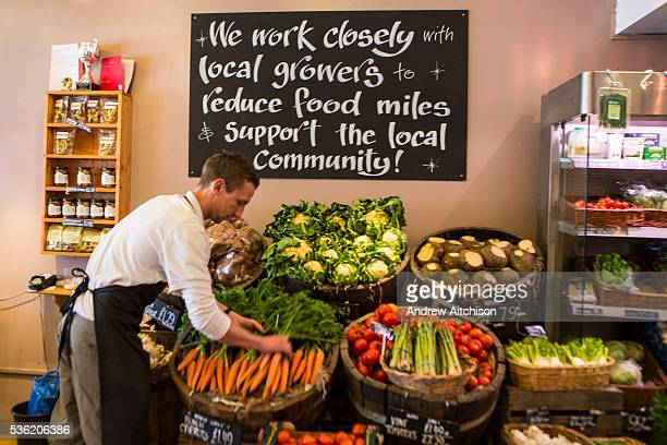 A male shop keeper arranges the carrots in a fruit and vegetable display within a connivence shop in Wadebridge North Cornwall United Kingdom The...