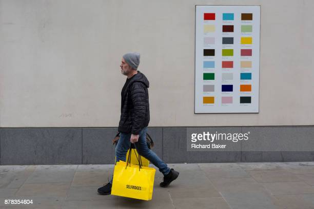 A male shopper carrying a yellow bag from Selfridges department store walks past a colour swatch on the wall of a central London business on 22nd...