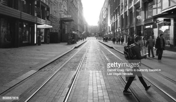 male shopper carrying bags walking across a street in downtown helsinki finland (black and white image) - black and white instant print stock pictures, royalty-free photos & images