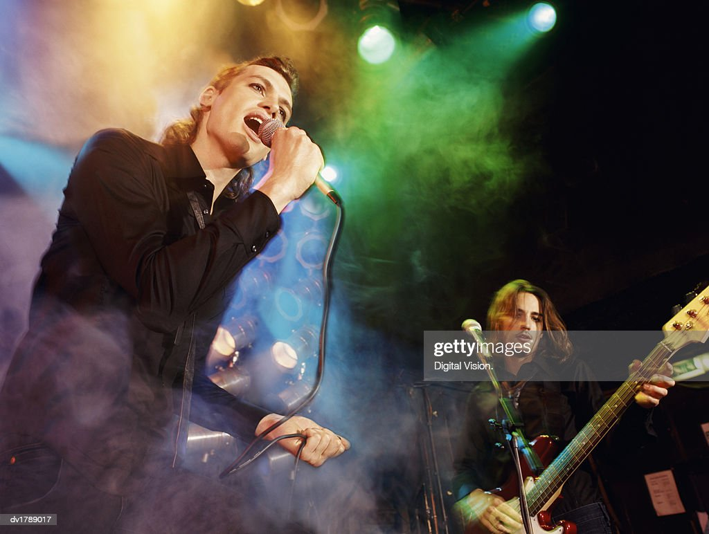 Male Singer and Guitarist in an Indie Band Perform on Smoky, Spotlit Stage : Stock Photo