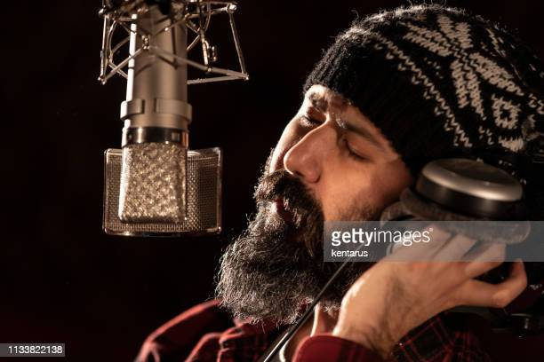 Male singer performing for recording in sound studio