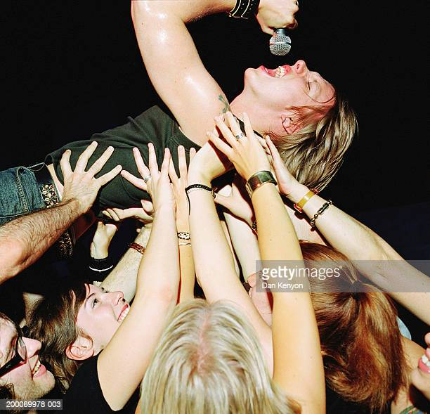 Male singer with microphone, crowd surfing