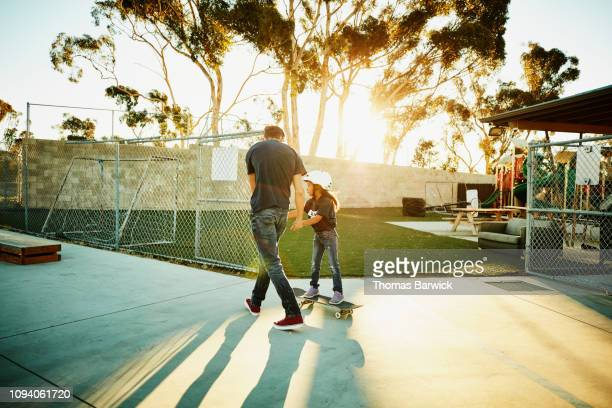 male skateboard instructor helping young female student learn to balance on board during summer camp - images stock-fotos und bilder