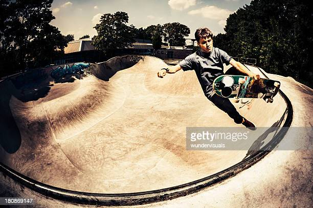 male skateboarder grabbing his skateboard - half pipe stock pictures, royalty-free photos & images