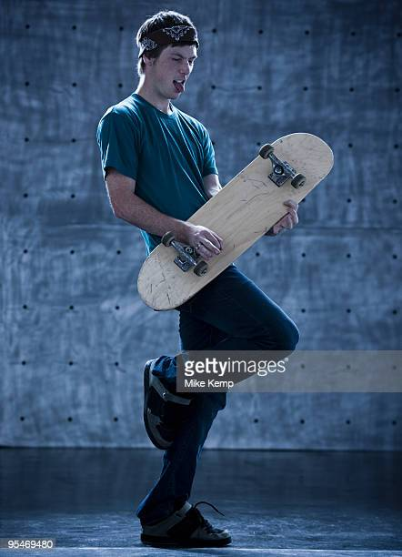 Male skateboarder playing air guitar